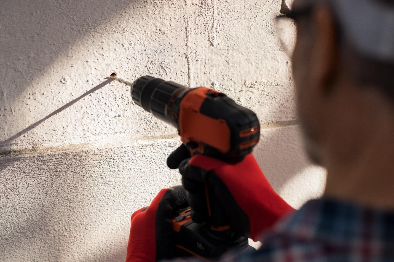 Мужчина сверлит дрелью отверстие в стене
